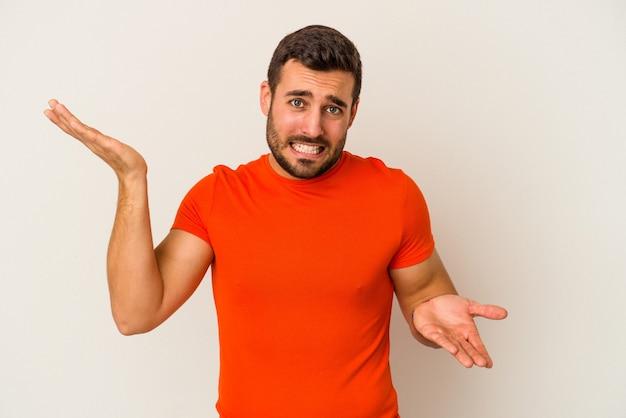 Giovane uomo caucasico isolato su sfondo bianco confuso e dubbioso scrollare le spalle per tenere uno spazio di copia.