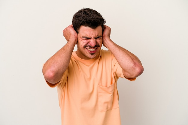 Giovane uomo caucasico isolato su sfondo bianco che copre le orecchie con le mani.