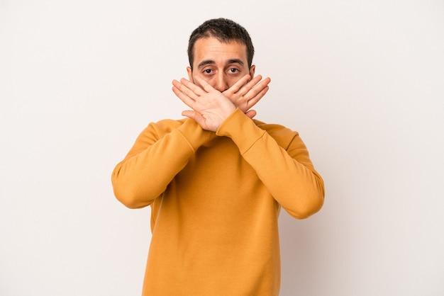 Giovane uomo caucasico isolato su sfondo bianco che fa un gesto di rifiuto