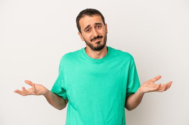Giovane uomo caucasico isolato su sfondo bianco dubitando e alzando le spalle nel gesto interrogativo.