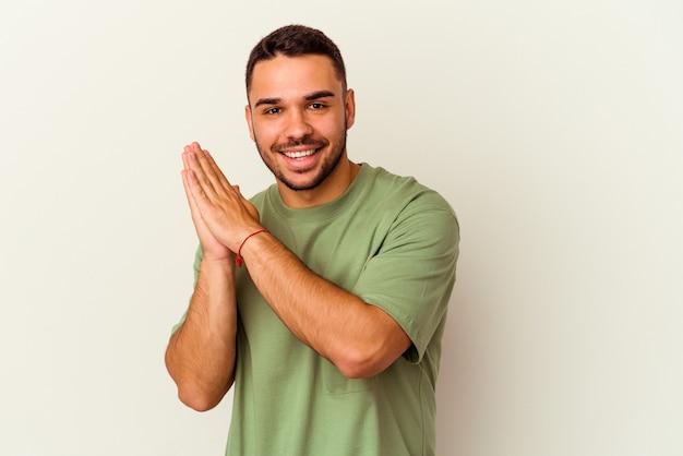 Giovane uomo caucasico isolato su sfondo bianco sentirsi energico e a suo agio, sfregandosi le mani sicure