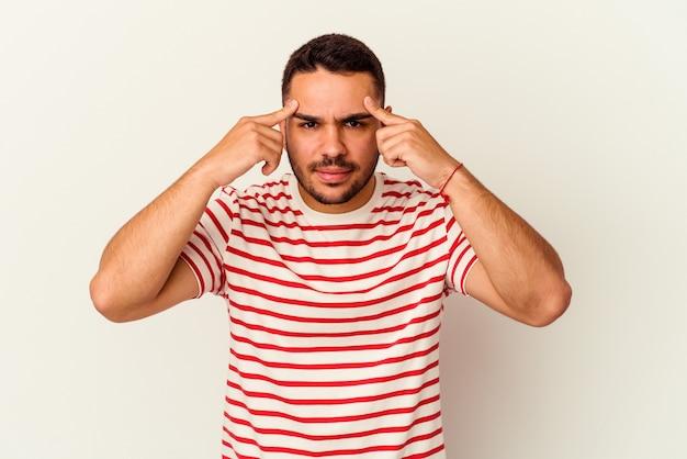 Il giovane uomo caucasico isolato su sfondo bianco si è concentrato su un compito, mantenendo l'indice rivolto verso la testa.