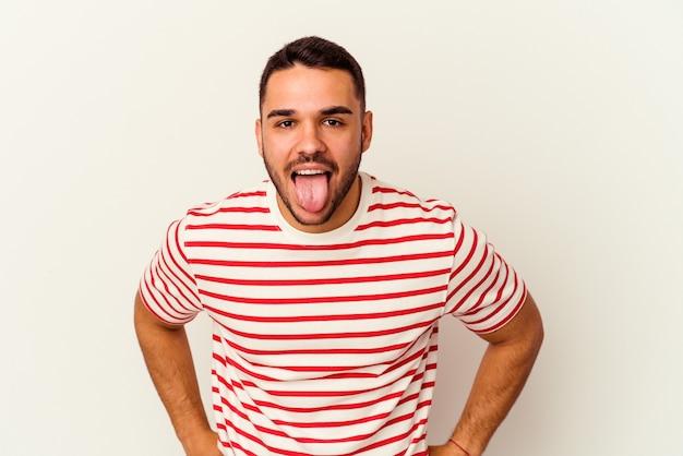 Giovane uomo caucasico isolato su sfondo bianco divertente e amichevole conficca fuori la lingua.