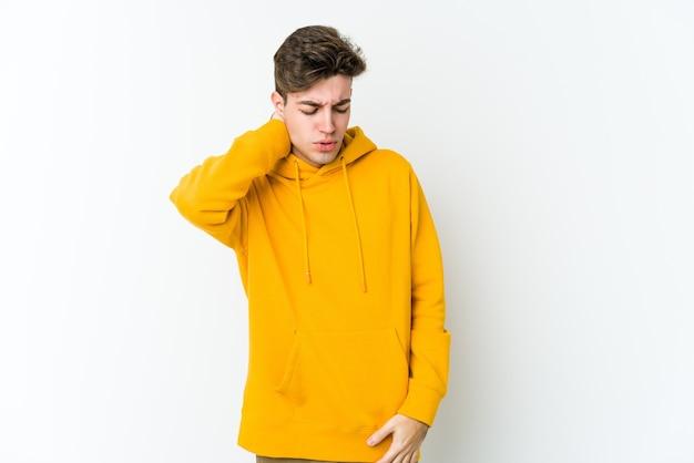 Giovane uomo caucasico isolato su sfondo bianco avendo un dolore al collo a causa dello stress, massaggiandolo e toccandolo con la mano.
