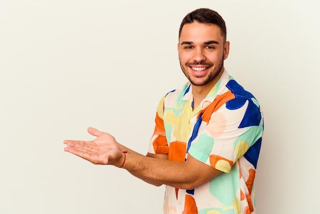 Giovane uomo caucasico isolato su sfondo bianco in possesso di uno spazio di copia su un palmo.