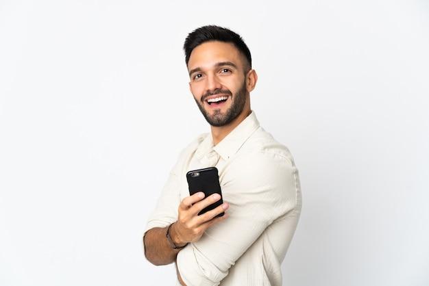 Giovane uomo caucasico isolato su sfondo bianco in possesso di un telefono cellulare e con le braccia incrociate