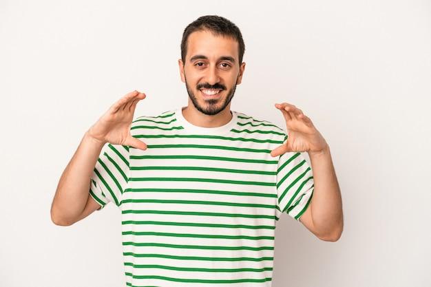 Giovane uomo caucasico isolato su sfondo bianco che tiene qualcosa con le palme, offrendo alla macchina fotografica.