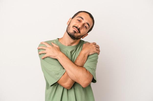Il giovane uomo caucasico isolato sugli abbracci bianchi del fondo, sorride spensierato e felice.