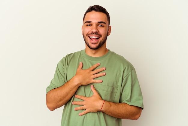 Il giovane uomo caucasico isolato su sfondo bianco ride felicemente e si diverte a tenere le mani sullo stomaco.