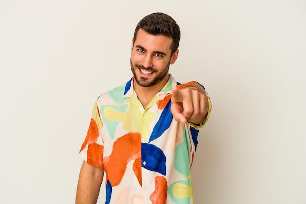 Giovane uomo caucasico isolato su sfondo bianco che punta alla parte anteriore con le dita.