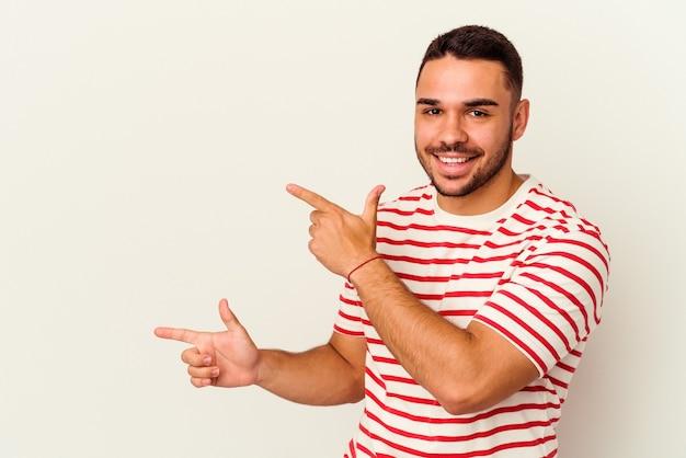 Giovane uomo caucasico isolato su sfondo bianco che indica con l'indice uno spazio di copia, esprimendo eccitazione e desiderio.