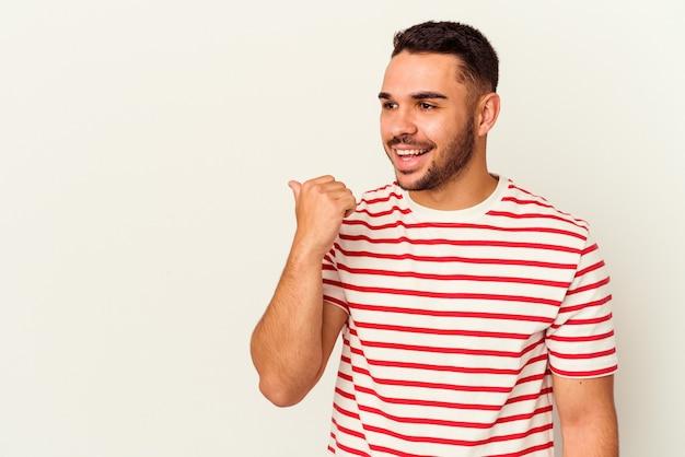 Il giovane uomo caucasico isolato su sfondo bianco indica con il dito pollice lontano, ridendo e spensierato.