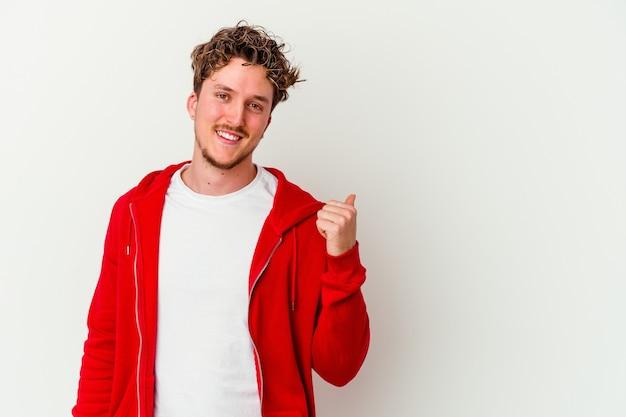 Giovane uomo caucasico isolato su sfondo bianco scioccato indicando con il dito indice uno spazio di copia.