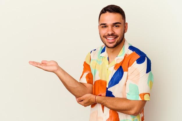 Giovane uomo caucasico isolato su sfondo bianco che mostra uno spazio di copia su un palmo e tiene un'altra mano sulla vita.