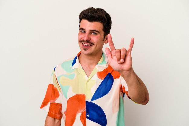 Giovane uomo caucasico isolato su sfondo bianco che mostra un gesto di corna come un concetto di rivoluzione.