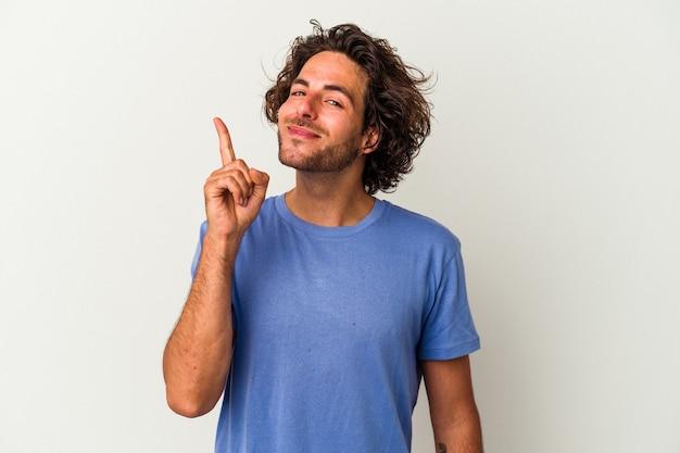Giovane uomo caucasico isolato su sfondo bianco che mostra il numero uno con il dito.