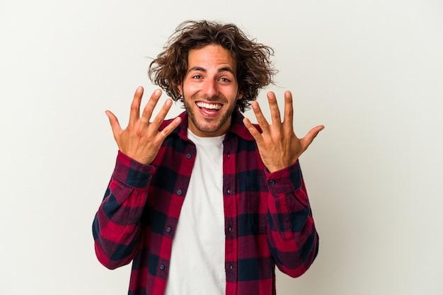 Giovane uomo caucasico isolato su sfondo bianco che mostra il numero dieci con le mani.