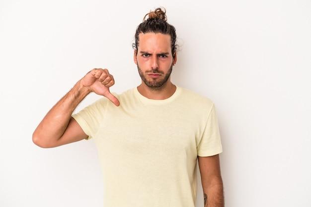 Giovane uomo caucasico isolato su sfondo bianco che mostra il pollice verso il basso, concetto di delusione.