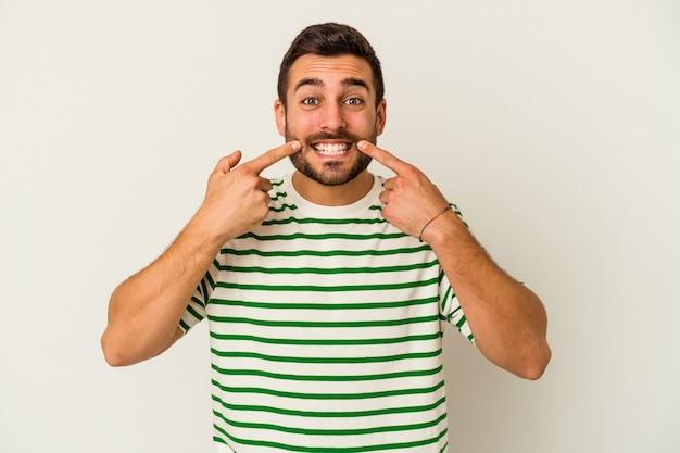 Giovane uomo caucasico isolato su sfondo bianco sorride, puntando le dita alla bocca.