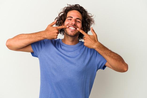 Giovane uomo caucasico isolato su sfondo bianco sorride, puntando il dito alla bocca.