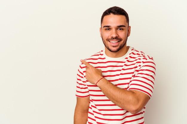 Giovane uomo caucasico isolato su sfondo bianco sorridente e rivolto da parte, mostrando qualcosa in uno spazio vuoto.