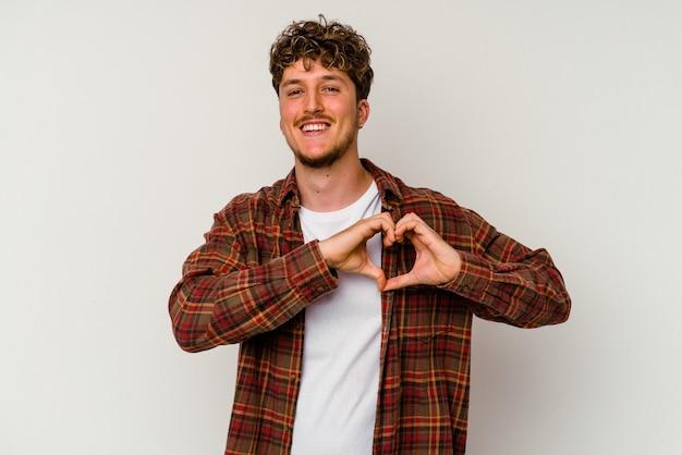 Giovane uomo caucasico isolato su sfondo bianco sorridente e mostrando una forma di cuore con le mani.