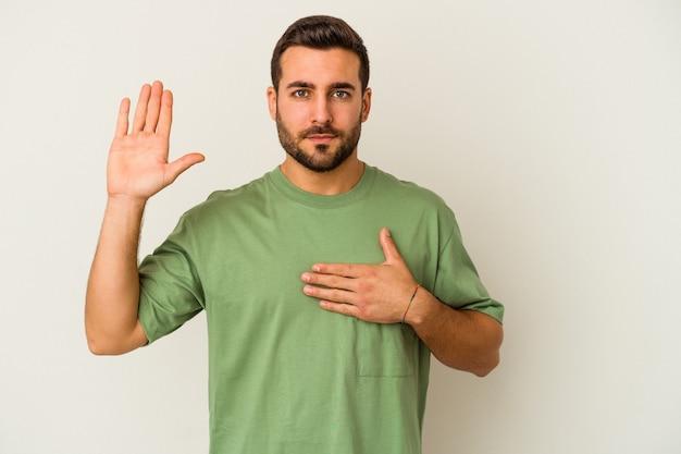 Giovane uomo caucasico isolato su sfondo bianco prestando giuramento, mettendo la mano sul petto.