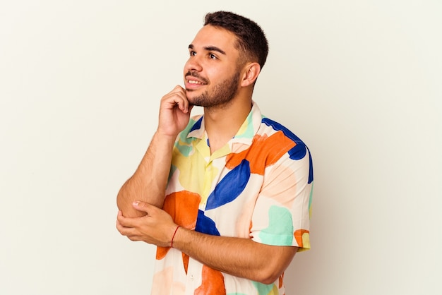 Giovane uomo caucasico isolato su sfondo bianco pensando e alzando lo sguardo, riflettendo, contemplando, avendo una fantasia.