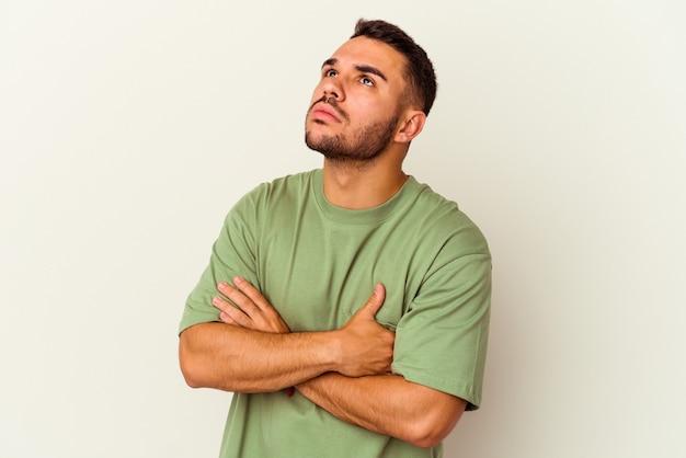 Giovane uomo caucasico isolato su sfondo bianco stanco di un compito ripetitivo.
