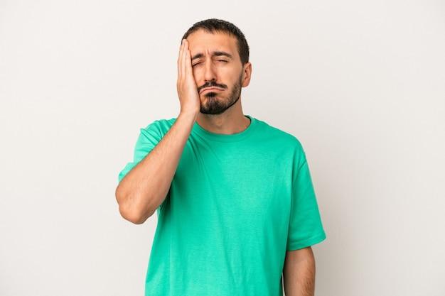 Giovane uomo caucasico isolato su sfondo bianco stanco e molto assonnato tenendo la mano sulla testa.