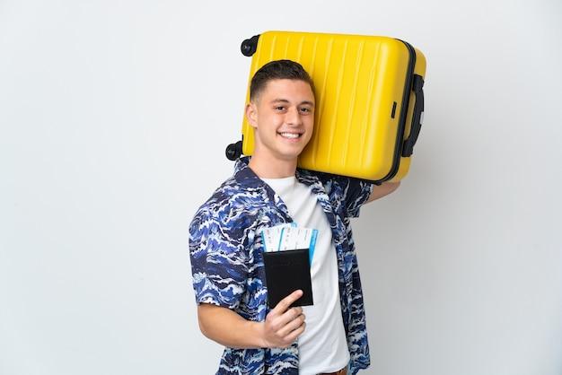Giovane uomo caucasico isolato su sfondo bianco in vacanza con la valigia e il passaporto