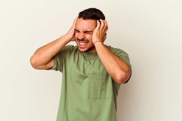 Giovane uomo caucasico isolato su bianco che copre le orecchie con le mani.
