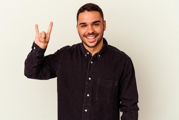 Giovane uomo caucasico isolato su bianco che mostra un gesto di corna come un concetto di rivoluzione.