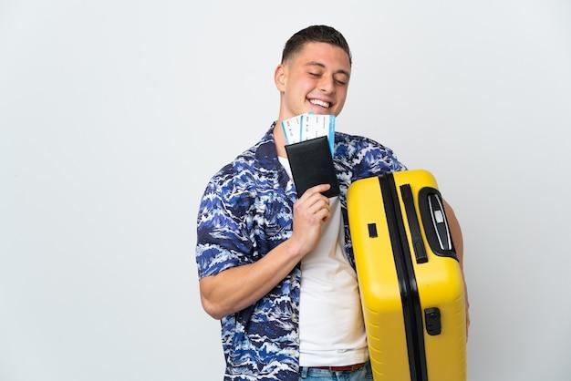 Giovane uomo caucasico isolato su bianco in vacanza con la valigia e il passaporto