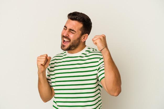 Giovane uomo caucasico isolato sul muro bianco ballando e divertendosi.