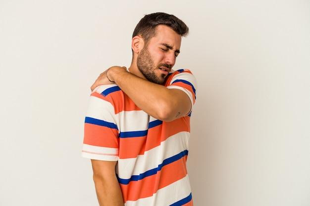 Giovane uomo caucasico isolato sulla parete bianca che ha un dolore alla spalla.
