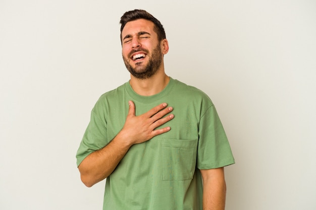 Il giovane uomo caucasico isolato sul muro bianco ride ad alta voce mantenendo la mano sul petto.