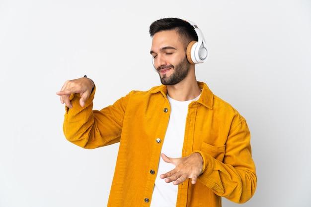 Giovane uomo caucasico isolato sulla parete bianca ascoltando musica e balli