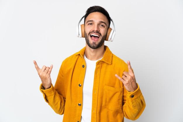 Giovane uomo caucasico isolato sulla musica d'ascolto della parete bianca che fa gesto della roccia