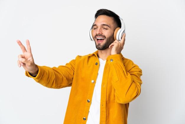 Giovane uomo caucasico isolato sulla parete bianca che ascolta musica e canto