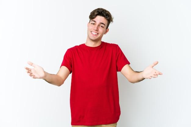 Giovane uomo caucasico isolato sul muro bianco che mostra un'espressione di benvenuto.