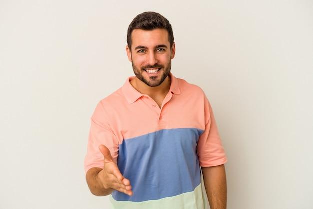 Giovane uomo caucasico isolato sul muro bianco che allunga la mano nel gesto di saluto.
