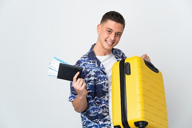 Giovane uomo caucasico isolato sul muro bianco in vacanza con la valigia e il passaporto