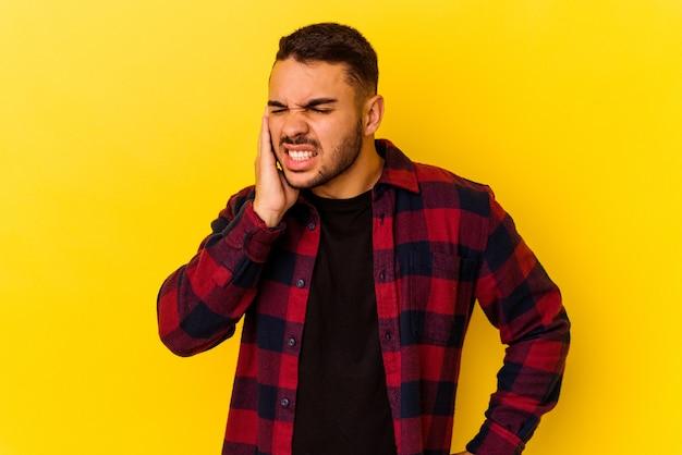 Giovane uomo caucasico isolato su sfondo giallo che copre le orecchie con le mani.