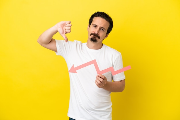 Giovane uomo caucasico isolato su sfondo giallo che tiene una freccia verso il basso e fa un cattivo segnale