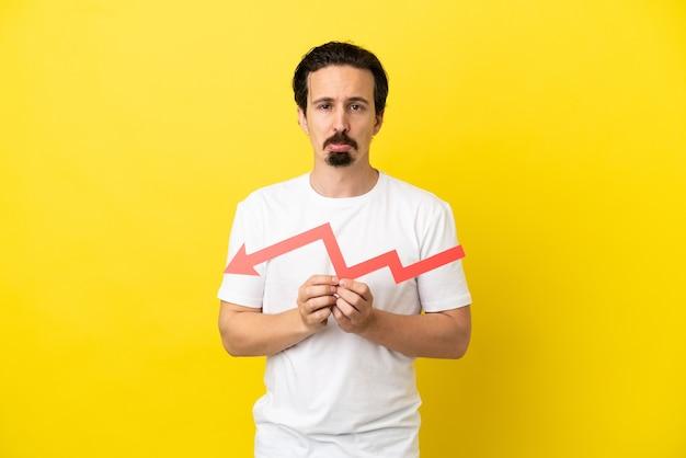 Giovane uomo caucasico isolato su sfondo giallo che tiene una freccia verso il basso e con espressione triste