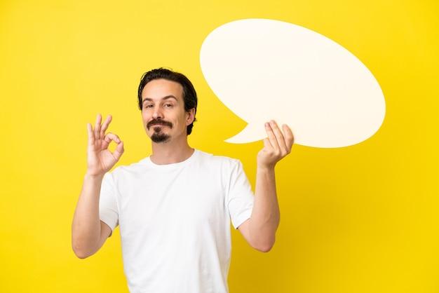 Giovane uomo caucasico isolato su sfondo giallo in possesso di un fumetto vuoto e facendo segno ok