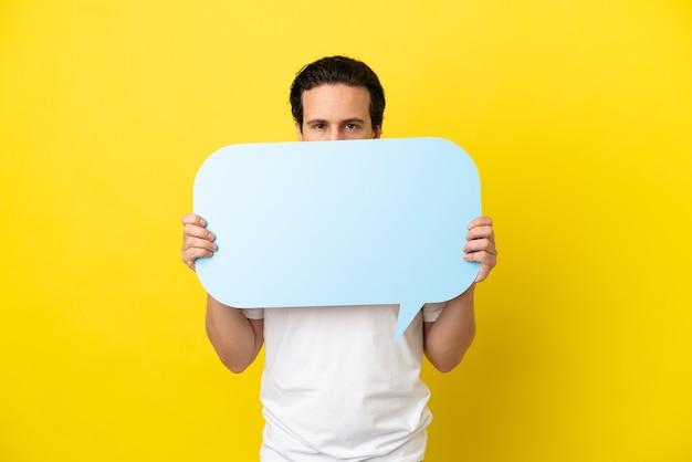 Giovane uomo caucasico isolato su sfondo giallo che tiene un fumetto vuoto che si nasconde dietro di esso nascondendosi dietro di esso