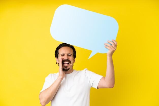 Giovane uomo caucasico isolato su sfondo giallo in possesso di un fumetto vuoto e gridando