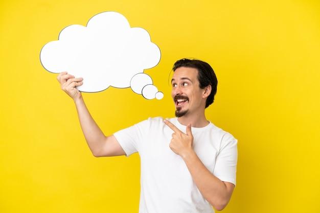 Giovane uomo caucasico isolato su sfondo giallo che tiene in mano un fumetto pensante e lo indica